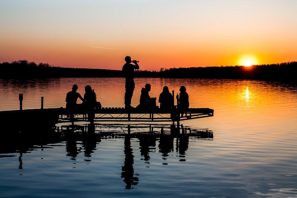 """Abendgruppe """"Lebenslust und Stille"""" - Eine Gruppe Menschen sitzen gemütlich auf einem Steg in einen See. Die Sonne geht in einem leuchtenden Orange unter."""